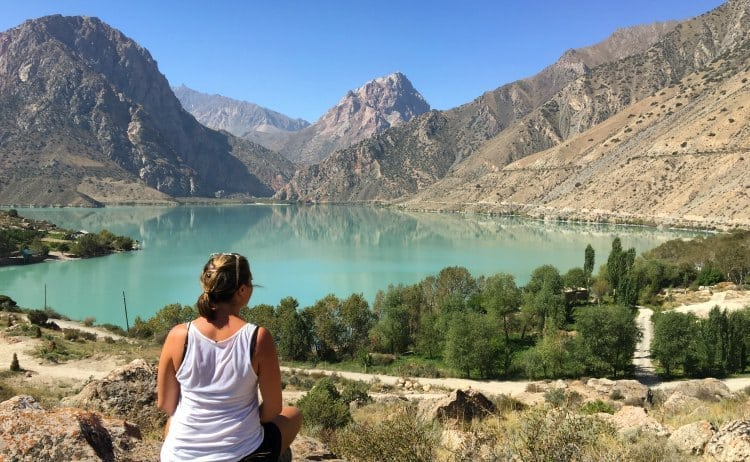 Image of woman sat by turquoise lake