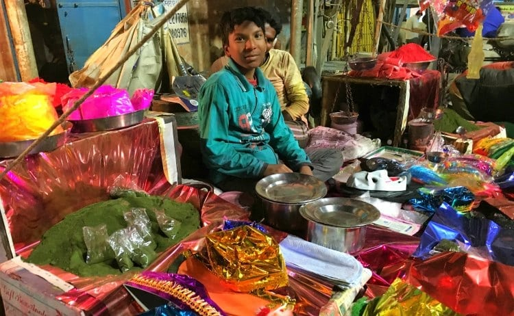 Image of indian boy selling coloured powder