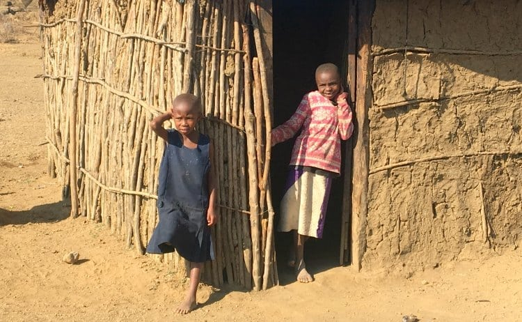 Image of two african children by mud hut