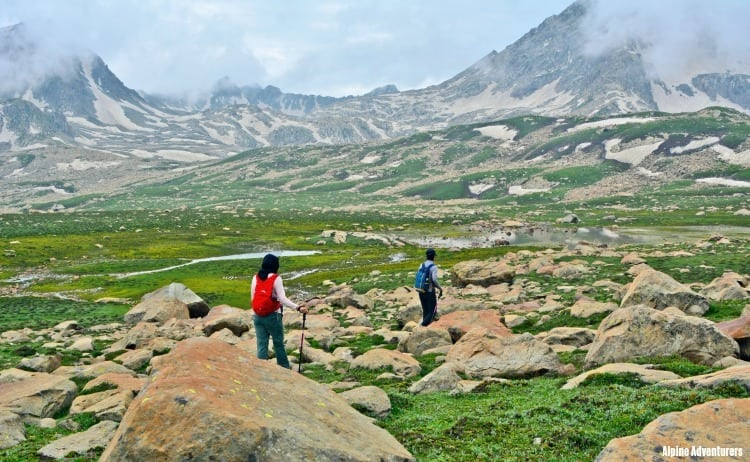 Image of 2 trekkers by alpine lake