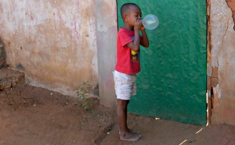 Image of Malagasy boy blowing up condom in Belo, Madagascar
