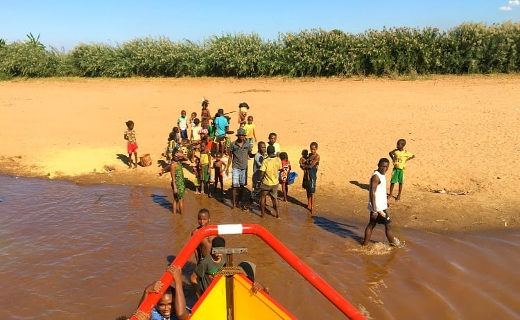 Malagasy villagers helping boat set sail on the Tsiribhina River