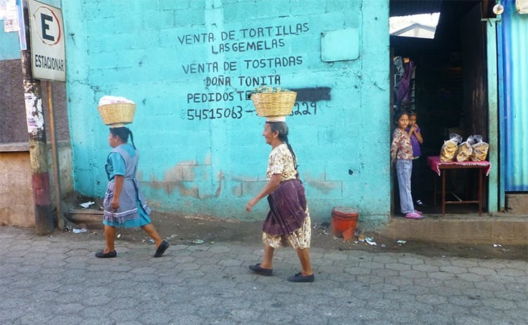 Guatemalan women carrying baskets on their heads in Cuidad Vieja, Antigua, Guatemala