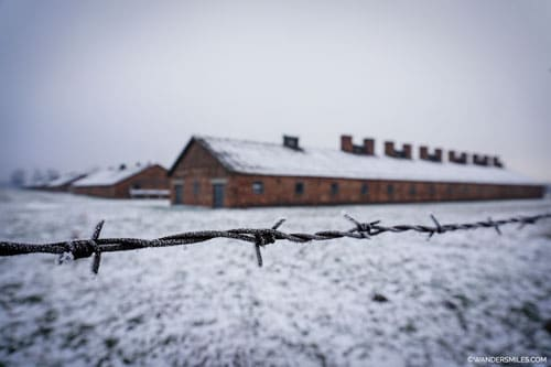 Barracks at the Birkenau concentration camp through barbed wire