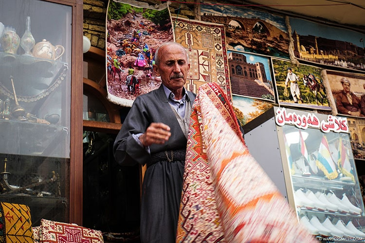 Kurdish man selling rugs in the bazaar of Erbil