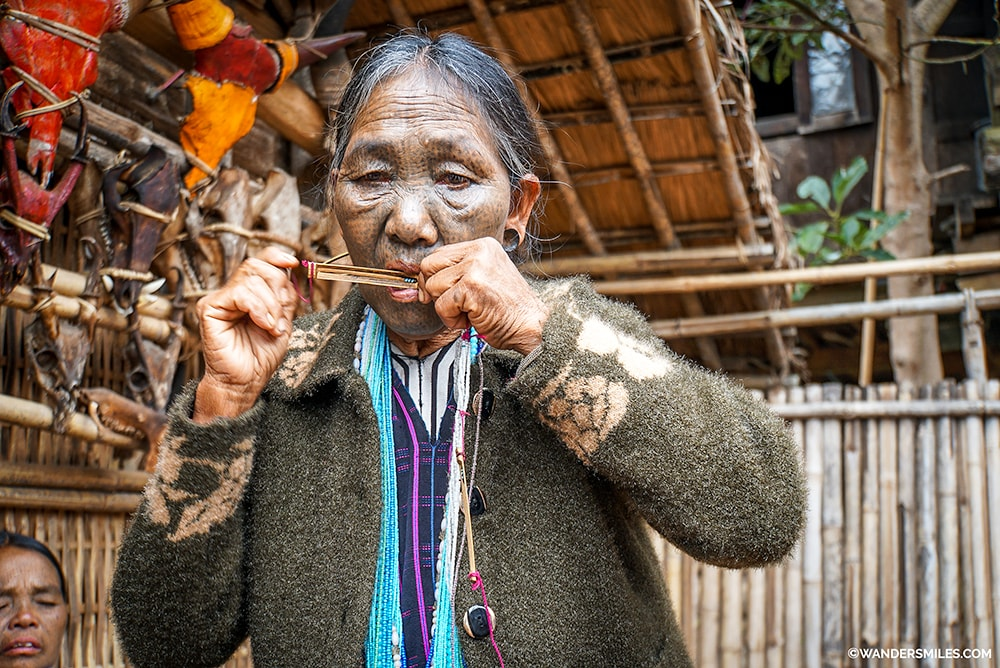 Face tattooed woman from the Dai Tribe playing an instrument