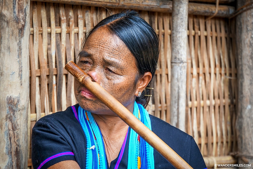 Fce tattooed woman from Dai Tribe in Myanmar playing nose flute