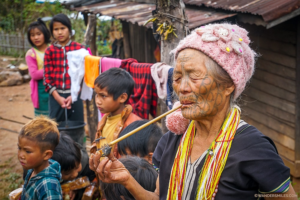 Old face tattooed woman from Muun Tribe with her Family
