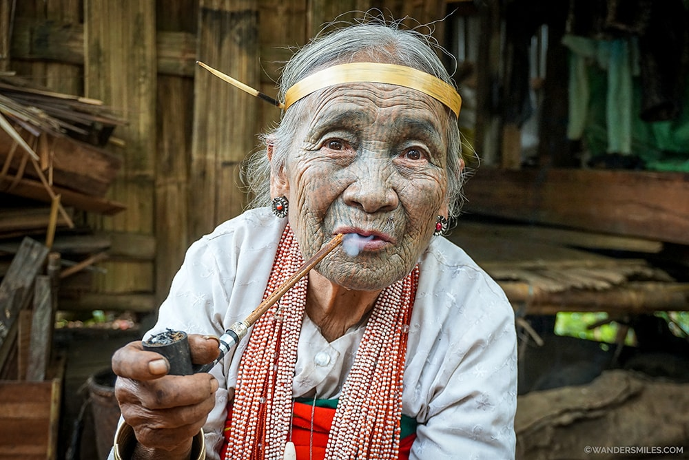 Face tattooed woman smoking from Yindu Tribe, Myanmar