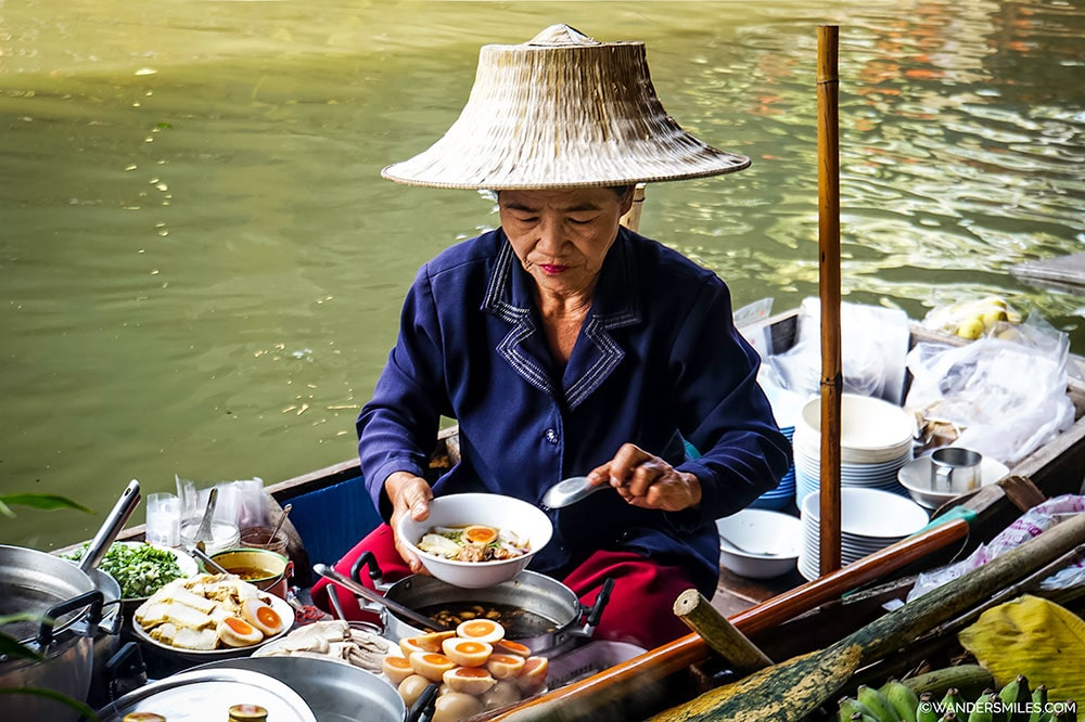 Old Thai woman cooking exotic local dishes from her boat in the bustling Damnoen Saduak floating market in Thailand