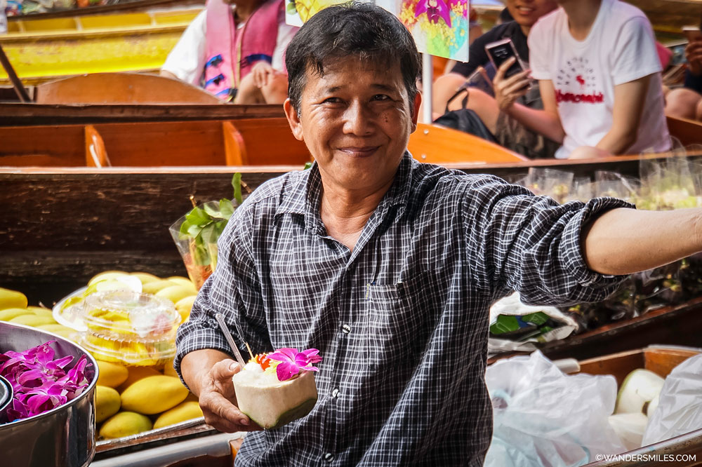 Thai man serving coconut ice cream from the bustling Damnoen Saduak floating market in Thailand