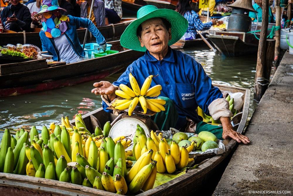 Old Thai woman selling fresh fruit in the bustling Damnoen Saduak floating market in Thailand