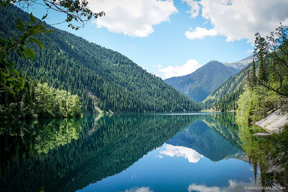 Stunning reflections of the green forest in Kolsai Lake 1, Kazakhstan