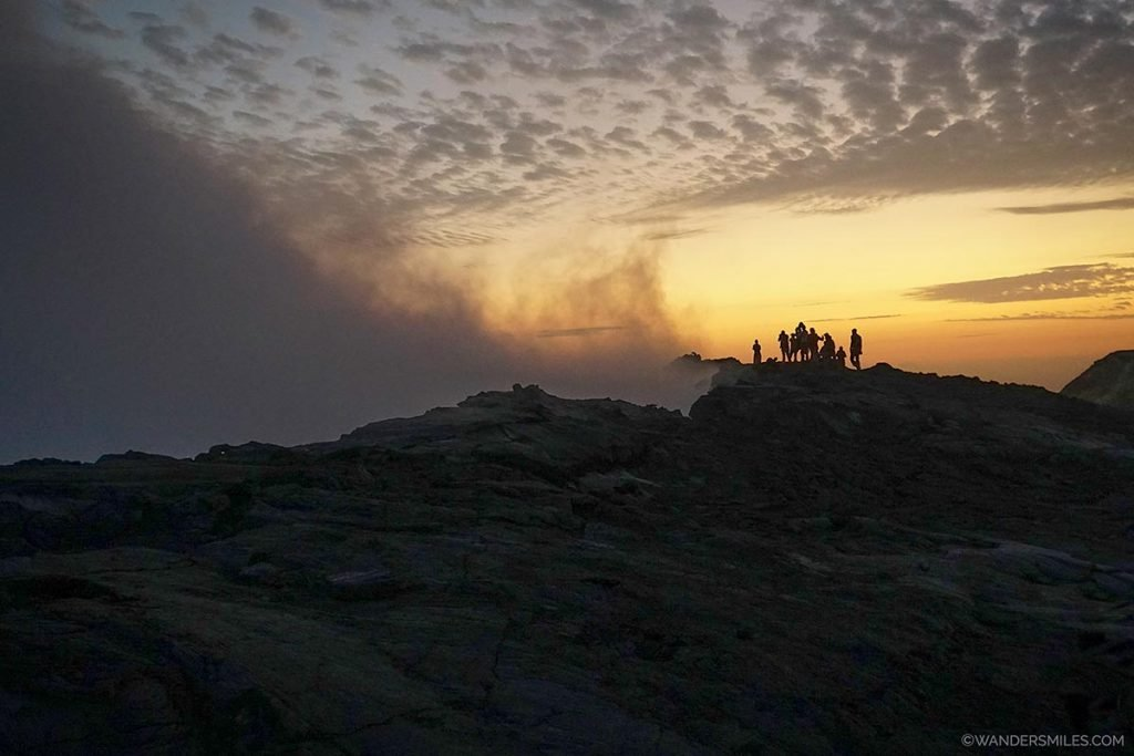 Sunrise and silhouettes of people by the Erta Ale volcano