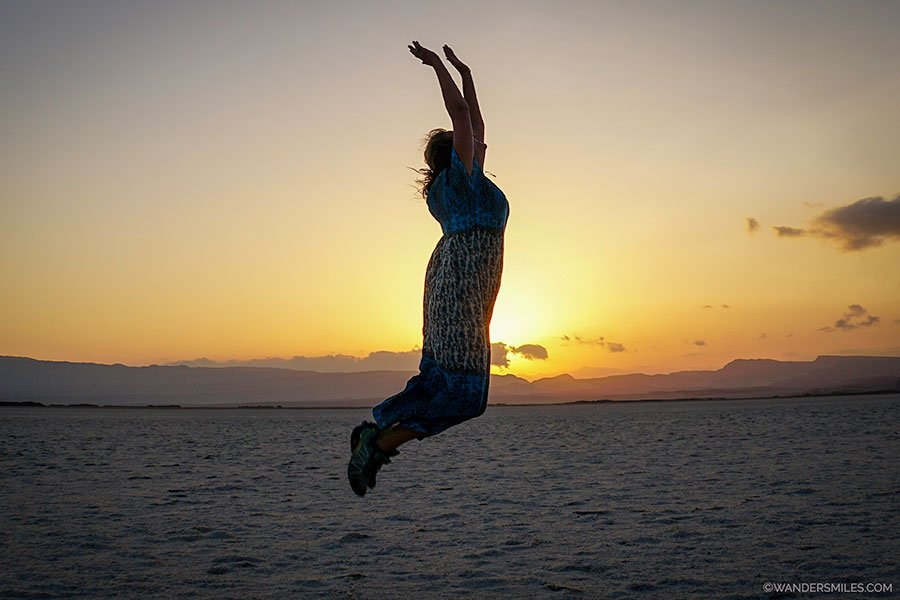 Vanessa from Wanders Miles jumping at sunrise at Lake Assal in Djibouti, East Africa