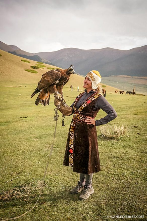 Vanessa from Wanders Miles travel blog holding golden eagle in Kyrgyzstan